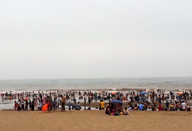 Ngay cạnh bến thuyền của ngư dân là bãi tắm với hàng nghìn du khách đang vui chơi