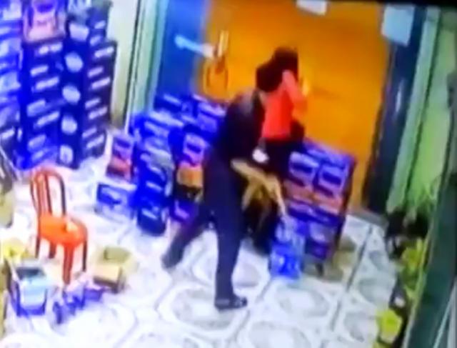 Người chồng dùng điếu cày đập liên tiếp vào mặt, vào người vợ (ảnh cắt từ clip)