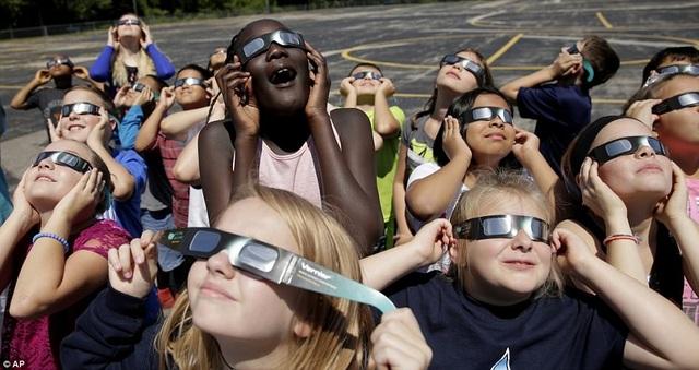 Nhật thực sẽ có quỹ đạo di chuyển xuyên Mỹ, khi vào buổi sáng người dân ở bờ biển Thái Bình Dương ở bang Oregon được quan sát hiện tượng này. 90 phút sau đó, người dân ở bang South Carolina sẽ có cơ hội chiêm ngưỡng nhật thực bên bờ Đại Tây Dương. Trong ảnh: Các em bé ở trường tiểu học Clardy, Kansas tập dượt dùng kính quan sát nhật thực (Ảnh: AP)