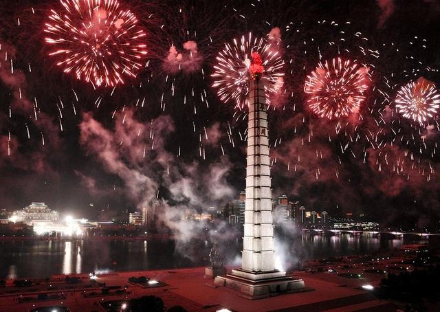 """Pháo hoa tại khu vực tháp Juche, biểu tượng của tinh thần Triều Tiên """"tự lực, tự cường"""" theo hệ tư tưởng cố lãnh đạo Kim Nhật Thành sáng lập nên. Ngọn tháp được xây dựng từ 25.500 viên đá trắng với ngọn đuốc đúc bằng kim loại nặng 45 tấn đặt bên trên với số viên đá tượng trưng cho tuổi đời của lãnh tụ Kim Nhật Thành cho đến thời điểm xây dựng. (Ảnh: KCNA)"""