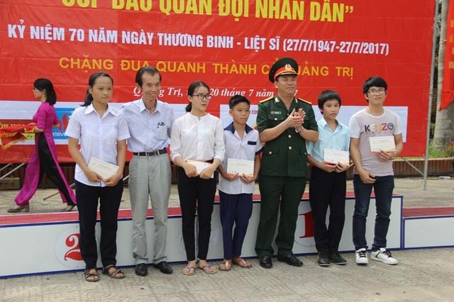Nhà báo Duy Thảo và đại diện Báo QĐND trao quà cho các em học sinh