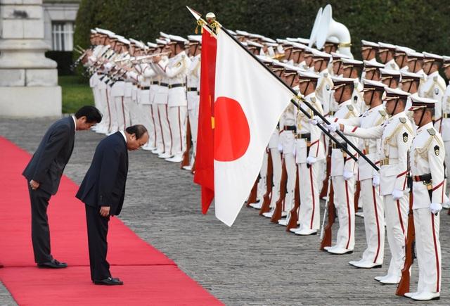 Lãnh đạo hai nước cúi chào quốc kỳ trước khi duyệt đội danh dự (Ảnh: Reuters)
