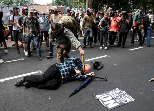 Một người biểu tình phản đối cuộc tuần hành tấn công một người theo chủ nghĩa ủng hộ da trắng trên đường phố Charlottesville. (Ảnh: Reuters)