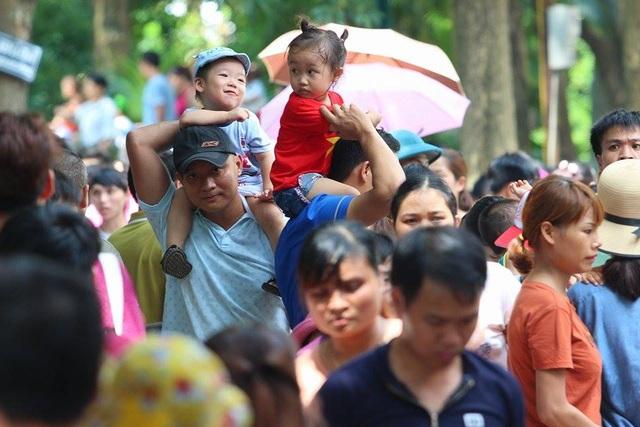Do quá đông đúc, nhiều ông bố đành phải chọn cách bế con lên cao để dễ di chuyển trong biển người.