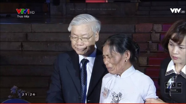 Tổng Bí thư Nguyễn Phú Trọng trực tiếp bước lên sân khấu chia sẻ nỗi xúc động, đỡ bà Khanh xuống ghế ngồi. (Ảnh: Nguyễn Dương)