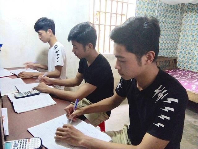 3 em Mạnh, Trọng và Vinh bên góc học tập đơn sơ.