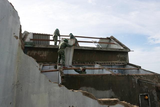 Các chiến sĩ biên phòng giúp một nhà dân lợp lại mái nhà.