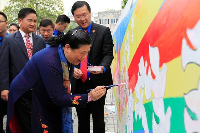 Bà Tòng Thị Phóng và anh Lê Quốc Phong tham gia hoạt động vẽ tranh cùng thanh niên Việt - Lào