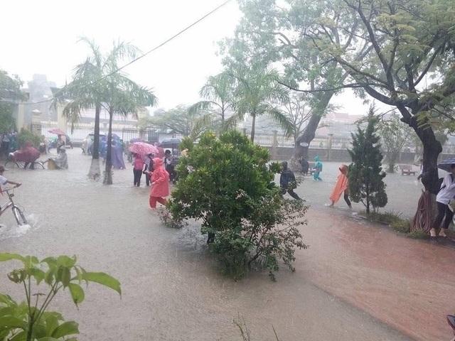 Các em học sinh phải lội nước vào lớp học.