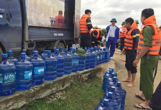 Tiếp tế lương thực, nước uống giúp người dân vùng lũ.