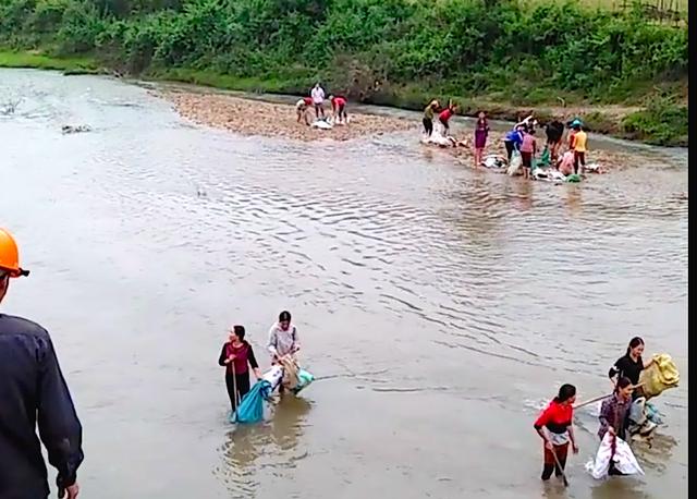 Người dân dùng bao bì xác rắn xúc cát từ lòng suối để gia cố bờ suối sạt lở.