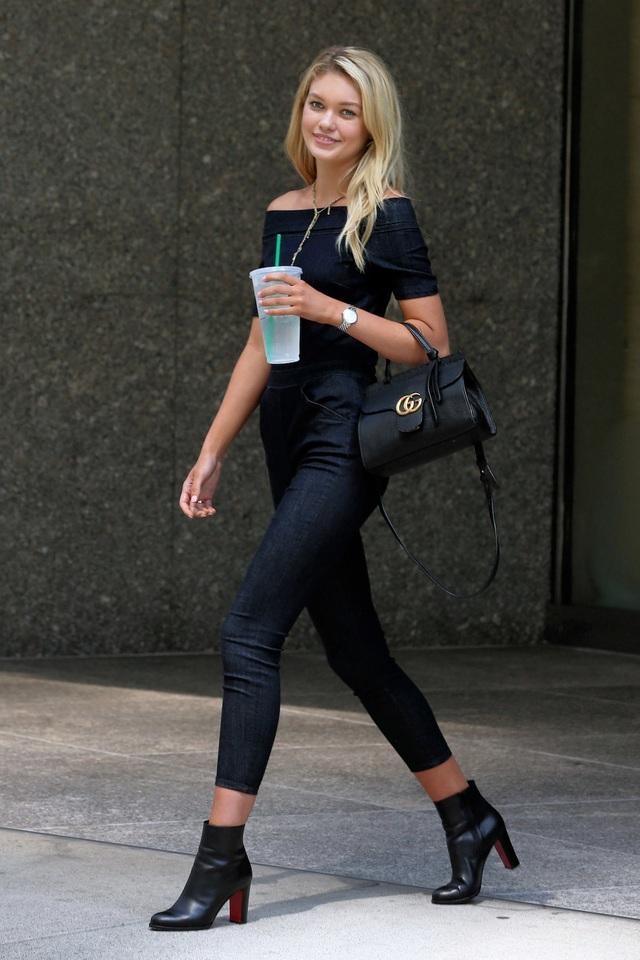 """Người mẫu Maggie Lane lựa chọn một bộ jumsuit denim tối màu khoe bờ vai gợi cảm. Cô lựa chọn đôi bốt cổ ngắn cùng tông màu để tạo cảm giác """"kéo dài"""" chân. Chiếc túi xách cùng tông đưa lại cho Lane vẻ đẹp thời trang """"ton sur ton""""."""