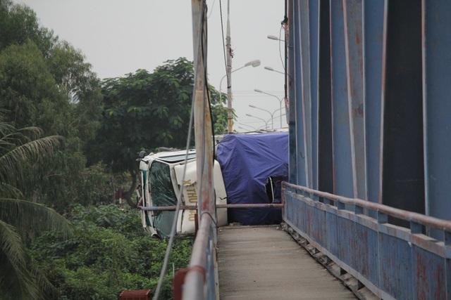 Xe ô tô húc tung lan can lao cả phần đầu xe ra ngoài thành cầu