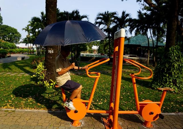 Ông Sáu vừa tập thể dục, vừa dùng ô (dù) để che nắng dù trời đã về chiều ở công viên Gia Định, quận Gò Vấp.