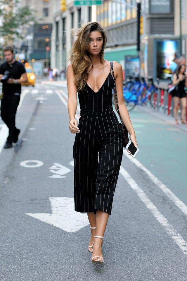 """Người mẫu Cindy Mello khác biệt khi lựa chọn bộ jumpsuit kẻ sọc tối màu. Phong cách thời trang với hai tông màu đen trắng """"monochrome"""" được Mello phối tinh tế khi màu giày trùng với màu sơn móng tay."""