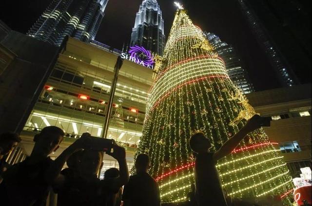 Du khách chụp hình bên cây thông Giáng sinh cạnh tòa tháp đôi Petronas ở Kuala Lumpur, Malaysia.