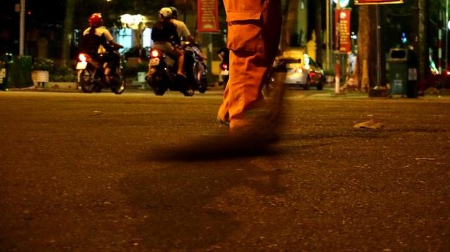 Đôi chân người công nhân quét đường vẫn lặng lẽ qua từng tuyến phố.