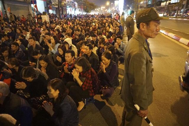 Những người dự lễ đứng ngồi dưới lòng đường.