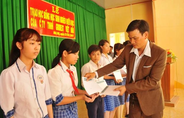 Ông Phùng Văn Công - Trưởng đại diện Công ty Grobest Việt Nam ở An Giang, Đồng Tháp trao học bổng cho các em học sinh trường THCS Nhị Mỹ