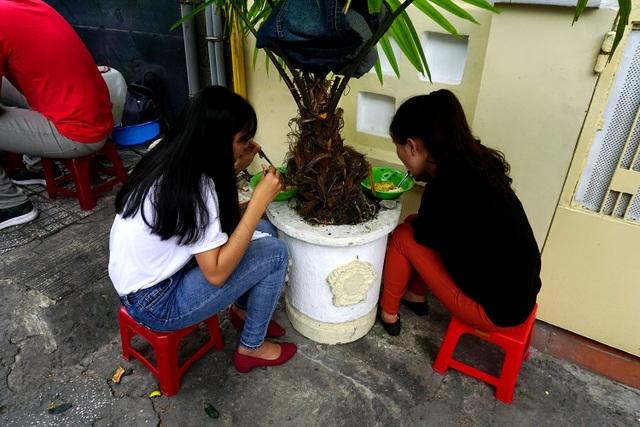 Hai cô gái dùng bữa trưa dưới gốc cây cảnh để tránh nắng.