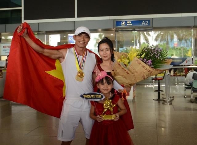 Vợ và con gái ra sân bay mừng anh chiến thắng trở về.