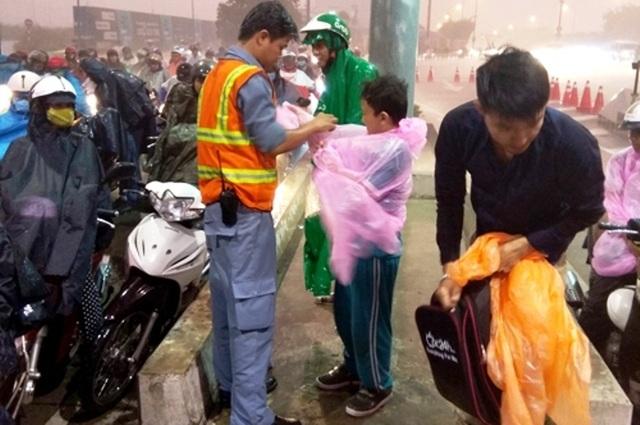 Đoàn viên thanh niên hầm Thủ Thiêm phát áo mưa miễn phí cho người dân không có áo mưa khi qua hầm Thủ Thiêm.