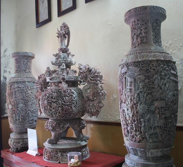 """Cảnh làng quê Việt với """"dòng sông, bến nước, con đò"""" được các nghệ nhân chạm khắc khá tinh tế trên hai chiếc lọ hoa."""