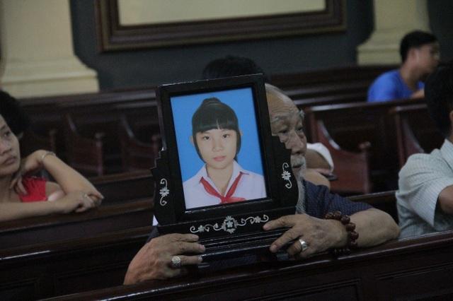 Gia đình bị hại mang di ảnh tới phiên tòa.