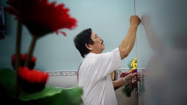 Thầy Huỳnh Thúc Tịnh, Hiệu trưởng trường phổ cập giáo dục phường 12, quận Bình Thạnh tự tay trang trí tấm bảng phông nền