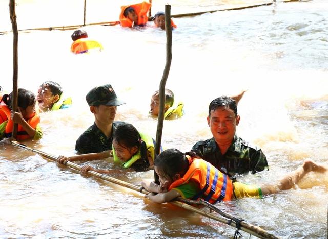 Trung tá Đặng Văn Trí - Đội phó đội vận động quần chúng Đồn biên phòng Bình Thạnh (người không đội nón) trực tiếp xuống sông cùng các chiến sĩ khác dạy bơi cho các em nhỏ xã Tân Hội và xã Bình Thạnh (ảnh: Phú Quí)