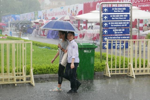 Hai nữ độc giả tuổi đời còn rất trẻ rời hội sách dưới mưa tầm tã, sau khi đã chọn được cho mình những cuốn sách ưng ý.