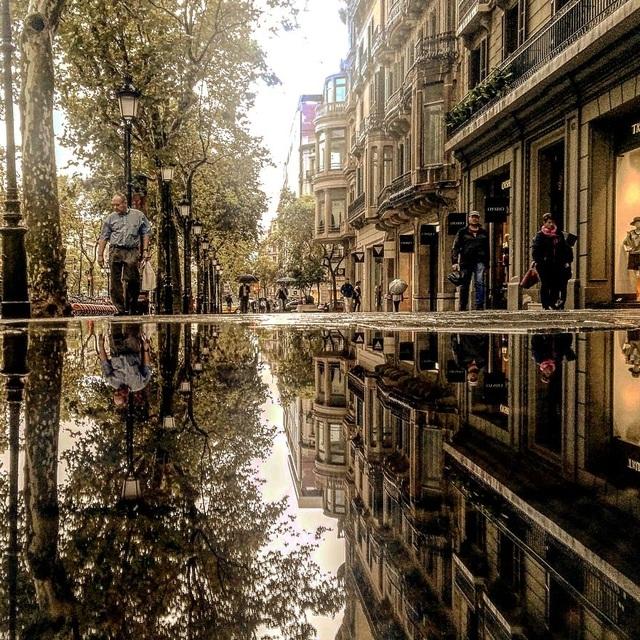 Thành phố Barcelona yên bình trong chiều thu qua phản chiếu từ vũng nước mưa.