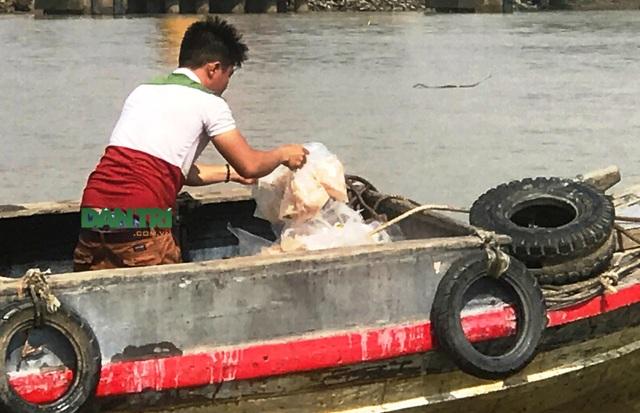 Rất đông người dân đã tranh nhau vớt cá basa đông lạnh trôi ra từ thùng hàng container.