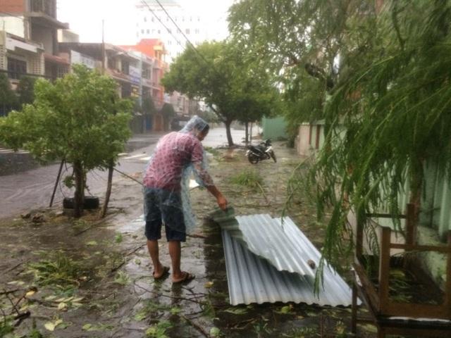 Người dân đi nhặt tấm tôn trong bão. (Ảnh: Trung Thi).
