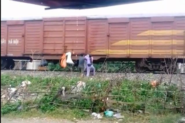 Nhiều bao tải rác được người dân cố treo vào thành tàu hỏa (ảnh cắt từ clip)