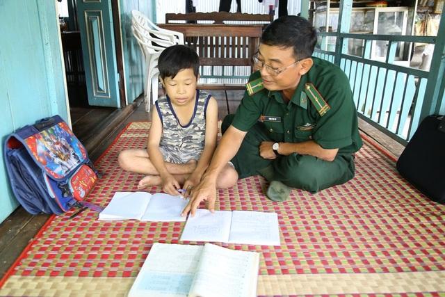 Thiếu tá Đặng Văn Trí, Đội phó vận động quần chúng, Đồn Biên phòng Bình Thạnh, hướng dẫn em Nguyễn Văn Thiện làm bài tập