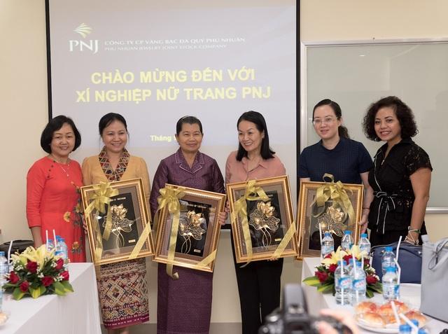 Bà Nguyễn Thị Cúc và Phạm Thị Mỹ Hạnh (váy đen) đại diện công ty tặng quà lưu niệm đến đoàn tham quan