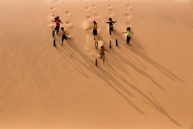 Ảnh đẹp trong ngày 2/8/2016. Một nhóm trẻ chơi đùa bằng vỏ bánh xe cũ tại đồi cát bay Mũi Né, Bình Thuận, Việt Nam.