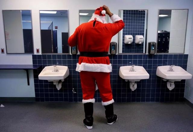 Một người đàn ông chuẩn bị trang phục ông già Noel trong phòng vệ sinh công cộng ở thành phố Boston, Mỹ.