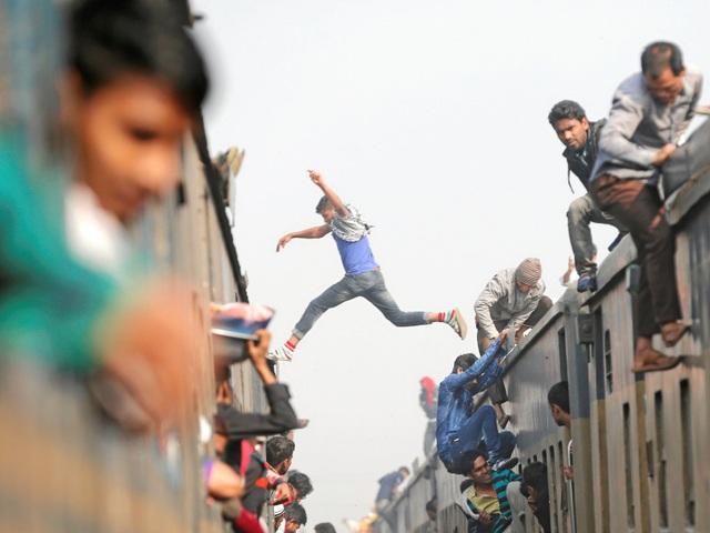 """Ở thành phố Dhaka, Bangladesh, mật độ dân cư ở mức 73.000 người trên mỗi diện tích đất 2,5 km2. Những chuyến tàu di chuyển xung quanh thành phố luôn đông đúc tới mức người ta trèo cả lên mái để có được một chỗ cho mình. Đối với những thanh niên trẻ mạo hiểm, họ còn luyện cả… """"kỹ năng"""" nhảy tàu."""