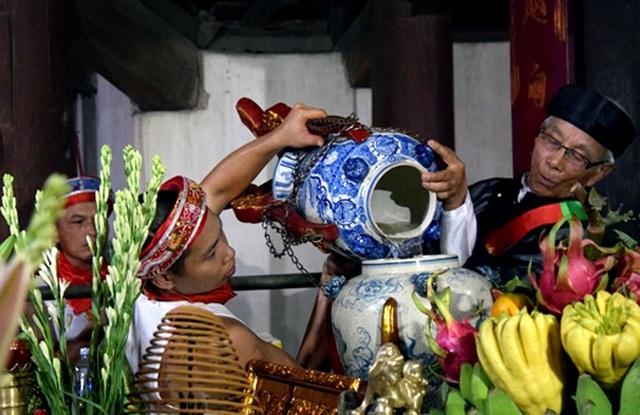 Cụ Từ đổ nước từ chóe vào chóe tại đình trong hậu cung để chuẩn bị mộc dục (Ảnh: Minh Lý)