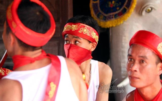 Đội khiêng kiệu dùng vải đỏ che miệng