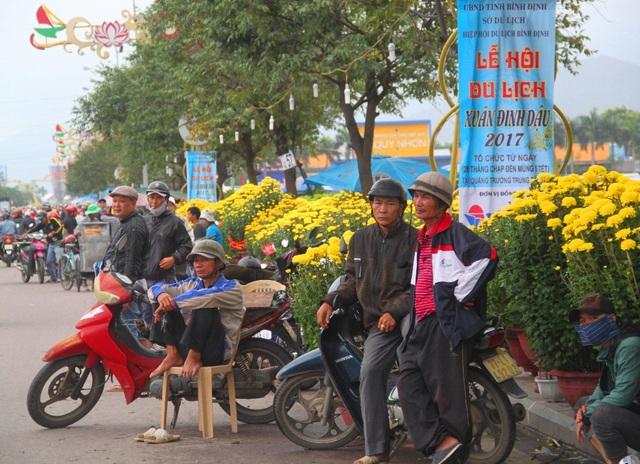 Ông Hùng (ngồi) cùng các xe thồ chở hoa cây cảnh thuê dịp Tết bạc mặt đứng ngồi đợi khách gọi chở hoa