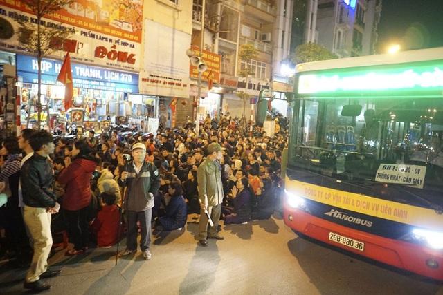 Chiếc xe buýt đi ngang qua khu vực làm lẽ, phải di chuyển sát với vị trí những người đang vái vọng từ ngoài đường.