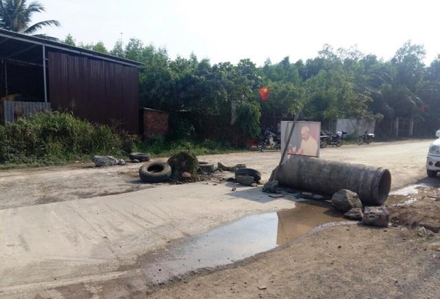Người dân dùng rào chắn để chặn đường không cho xe tải ra vào mỏ đá.