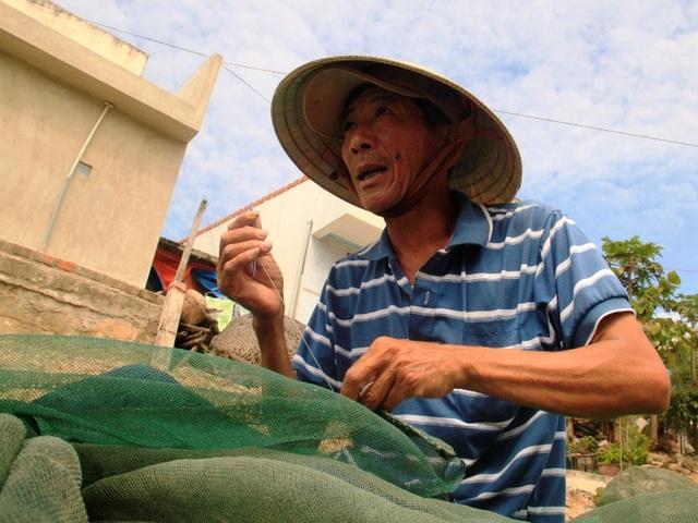 Ngư dân Huỳnh Công Chính đang tranh thủ vá lưới chuẩn bị cho chuyến biển sắp tới