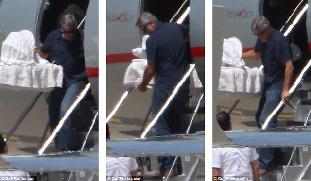 Nam tài tử rất cẩn thận khi di chuyển chiếc nôi có con nhỏ nằm trong từ trên máy bay xuống tới chiếc xe hơi chờ sẵn.