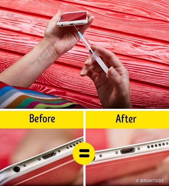 Sử dụng ống xy lanh và kim tiêm để thổi bay bụi bám trên các khe kẽ của điện thoại.