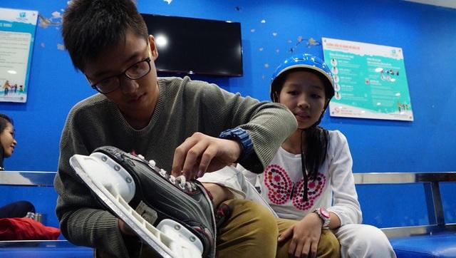 Bạn Lê Xuân Vĩnh đang chỉnh lại giày cho em gái