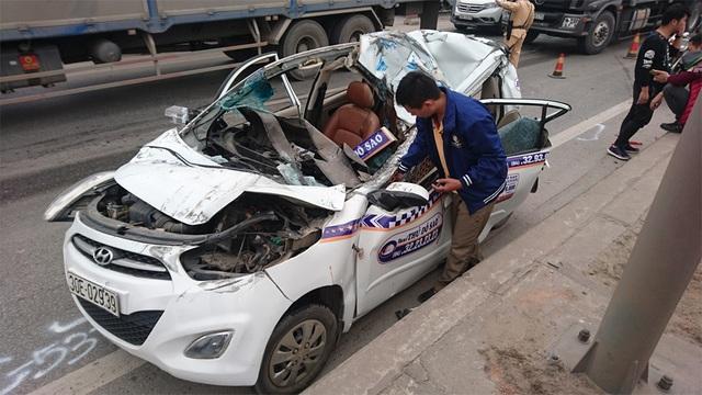 Anh Bình kiểm tra đồ đạc bị rơi trong xe taxi bẹp dúm sau vụ tai nạn.